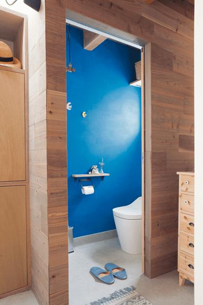 古材風の板張り壁とブルーのペイントがコントラストのトイレ
