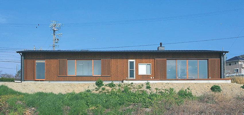 海岸から眺めた焦げ茶色の平屋建ての家外観