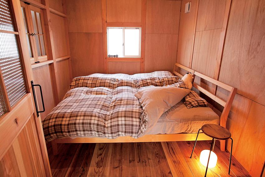 木に囲まれたコンパクトな寝室