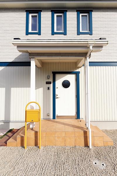 白と青にポストの黄色が差し色となった玄関
