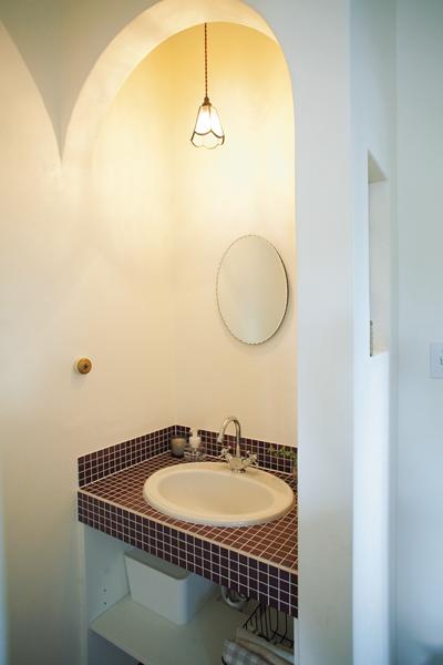 ボルドー色のモザイクタイルが印象的な手洗いコーナー
