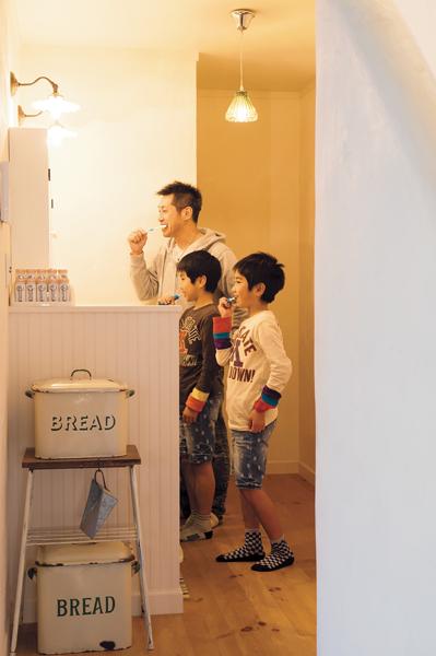 洗面コーナーで歯磨きをする家族