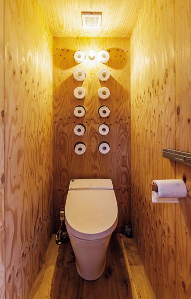 背面の壁にトイレットペーパーが収納されたトイレ