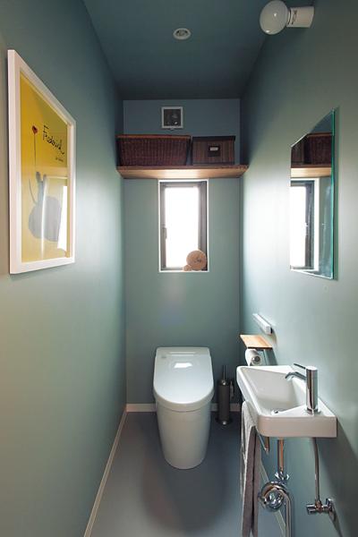 ブルーグレーの壁紙のトイレ