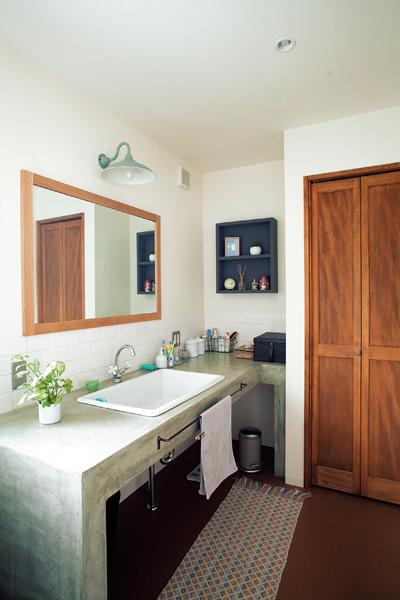 モルタル塗りの洗面台がある洗面室